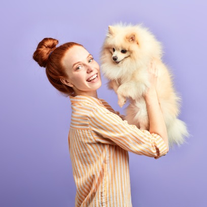Woman with red hair holding fluffy dog up against purple wall