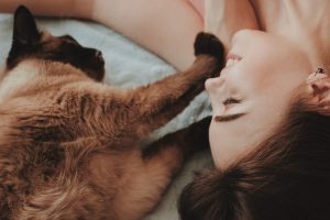 woman lying with her brown cat