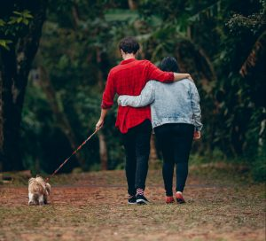 man and woman walking a dog in the park