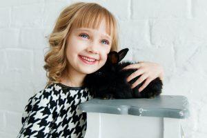 little blonde girl holding black rabbit