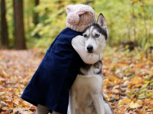 young girl hugging dog in leaves