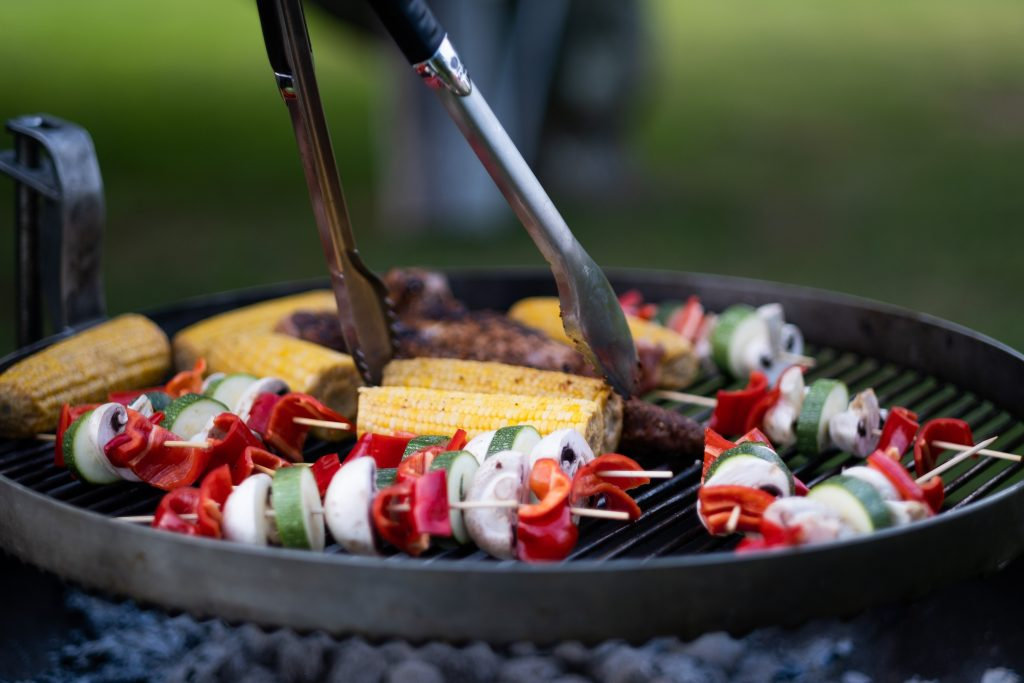 barbeque cooking chicken skewers and corn on the cob